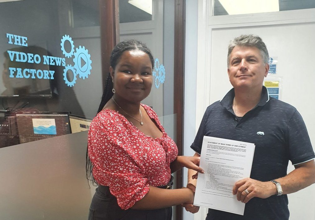 Joanna and John shake hands whilst holding her new contract.